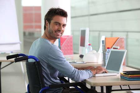 silla de ruedas: El hombre sentado en el escritorio en silla de ruedas Foto de archivo