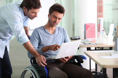 Businessman in wheelchair with laptop computer photo