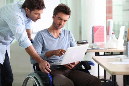 discapacidad: Hombre de negocios en silla de ruedas con ordenador portátil