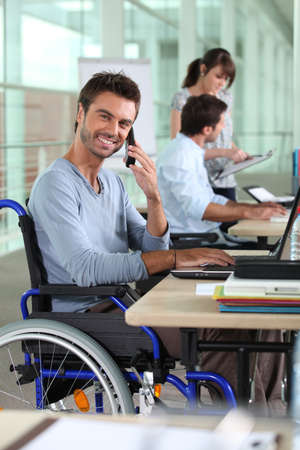 Smiling man in a wheelchair working in an office photo