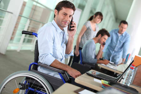 discapacidad: Hombre en silla de ruedas con el teléfono móvil en el trabajo