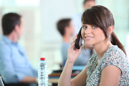 front office: Woman with mobile phone colleagues sat in background Stock Photo