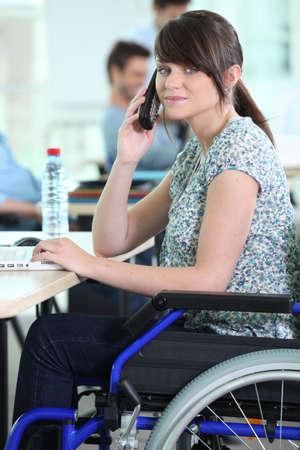 toegangscontrole: Jonge vrouw in een rolstoel op haar bureau Stockfoto