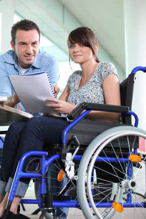 personas discapacitadas: Oficina de discapacitados mujer trabajaba junto a su colega Foto de archivo