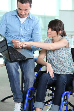 Young woman in wheelchair being shown something on a laptop computer photo