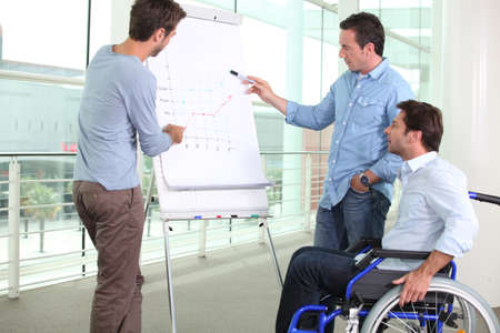 Man in wheelchair with colleagues photo
