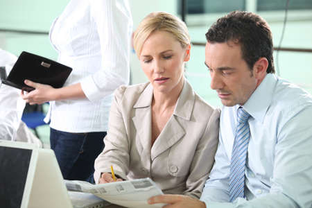 Business colleagues looking at a newspaper photo