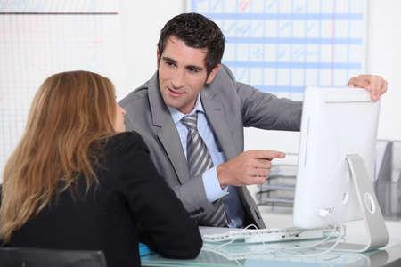interpret: Man showing woman computer screen