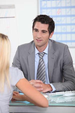 rapport: Man sat at desk talking to blond female
