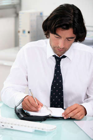 Businessman noting appointment on organizer Stock Photo - 13817929