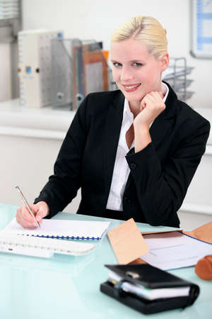 Young woman smiling sitting at a desk Stock Photo - 13817915