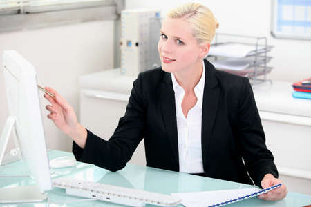 clerical: Blonde woman working at a clean modern desk
