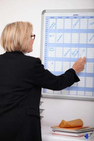 cronogramas: Escrito empresaria madura en un planificador de la pared