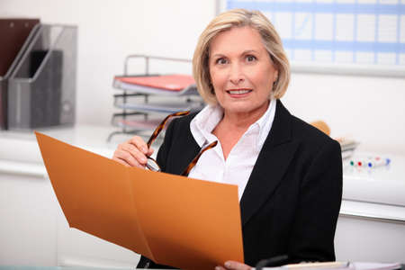 Mature businesswoman holding an open file photo