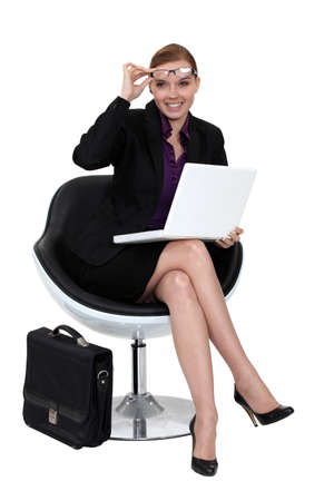 business woman legs: A businesswoman sitting in a modern chair. Stock Photo
