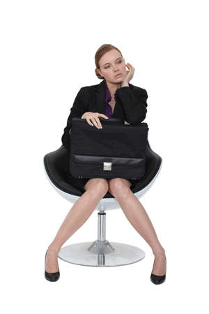Austere businesswoman sitting in a chair with a briefcase on her lap photo