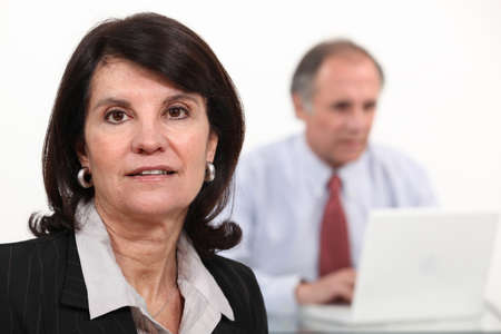 Mature businesswoman and man using a laptop photo