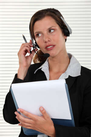 Woman listening to a call on her headset Stock Photo - 13844620