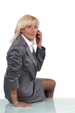 perched: Senior businesswoman perched on desk during call Stock Photo
