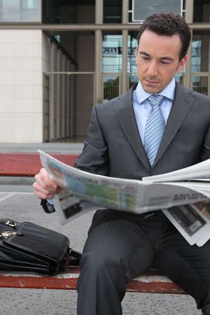 Businessman reading a newspaper photo