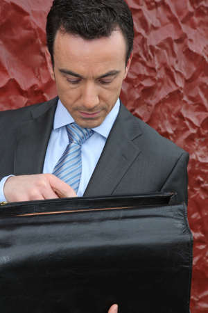 suit case: Businessman looking in his briefcase