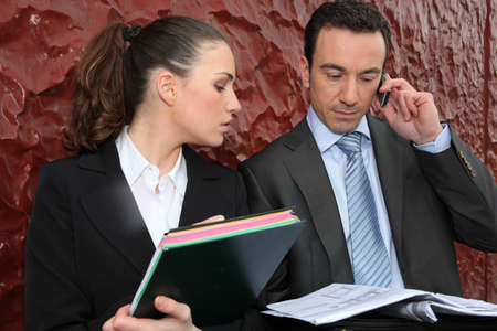Business couple looking at a newspaper and making a phone call Stock Photo - 13850261