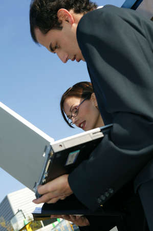verifying: Co-workers with laptop outdoors Stock Photo