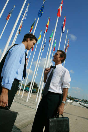 diplomats: Two diplomats stood by national flags