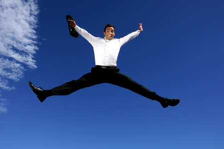 Businessman with briefcase jumping for joy photo