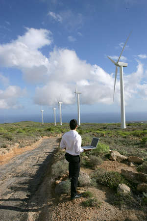 Entrepreneur with laptop observing wind turbines Stock Photo - 13850313