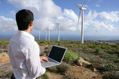 Man with laptop in wind farm photo