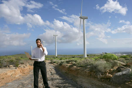 Man with a phone and laptop on a wind farm photo