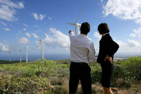 Business couple standing in a field of wind turbines photo