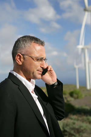 rural development: Businessman talking on his mobile phone in a wind turbine park