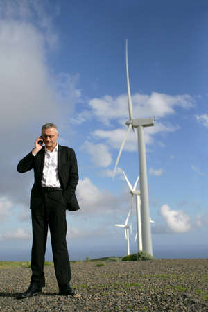 nonpolluting: Man on phone in front of wind turbines