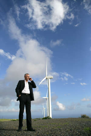 facing to camera: Man on the telephone next to a wind turbine
