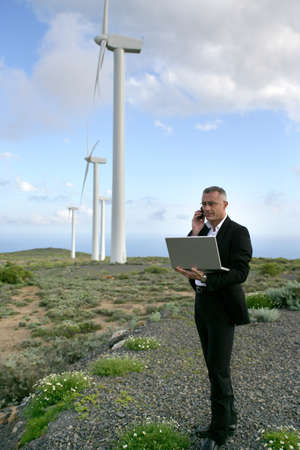 Businessman using a laptop on a windfarm photo