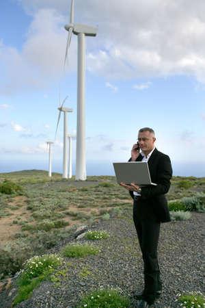eolian: Businessman using a laptop on a windfarm