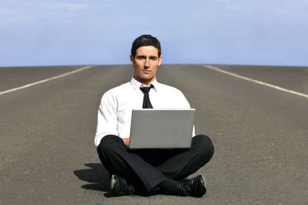 Man alone with laptop on airstrip photo