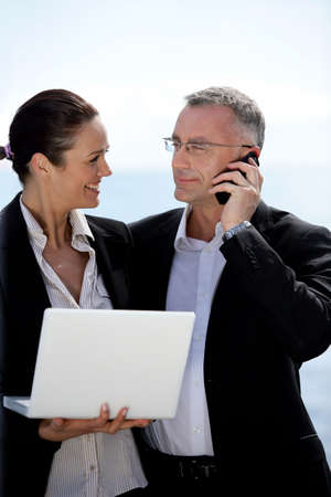 Business couple standing outdoors with a laptop and a phone Stock Photo - 13828069