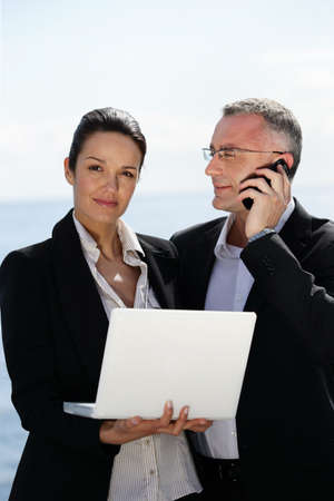 collaborator: Businesswoman with laptop next to a collaborator on phone