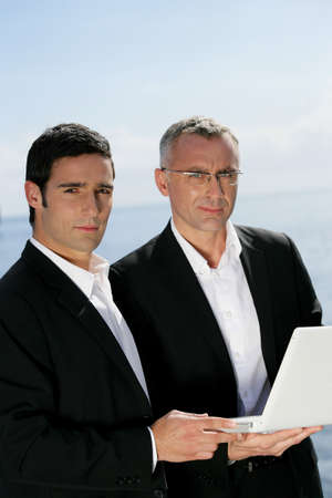 collaborators: Two businessmen outdoors with laptop