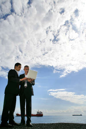 Businessmen using a laptop against a blue sky with fluffy clouds photo