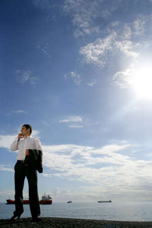 Businessman on the phone standing by the ocean with tankers in the background photo