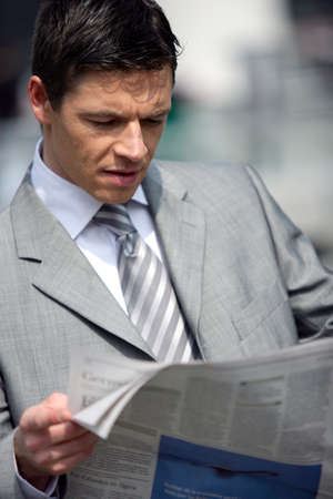 serious businessman: Businessman reading newspaper outdoors Stock Photo