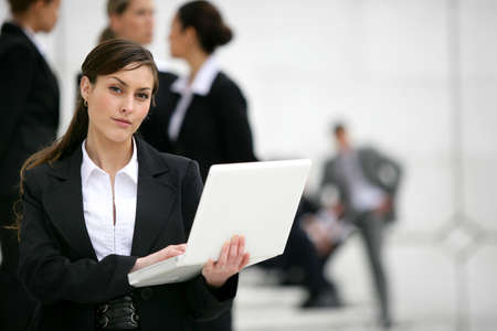 Businesswoman with laptop stood outside workplace photo