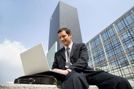 remote access: Businessman using his laptop in the city Stock Photo