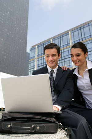 accomplices: Businessman and businesswoman laughing in front of a laptop outdoors