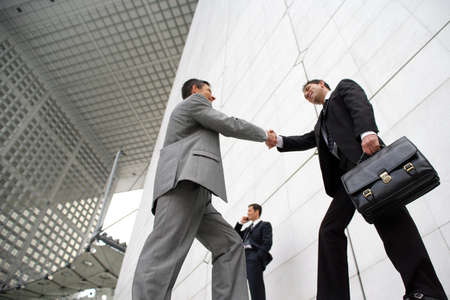 negotiation business: Businessmen shaking hands outside