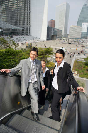 Business people on an escalator photo